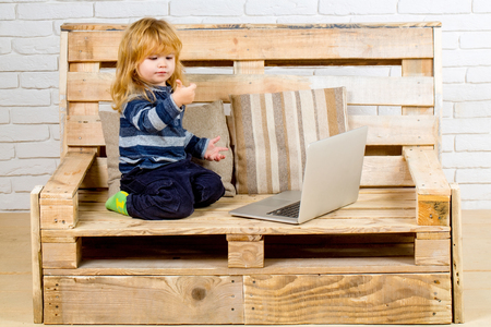child with laptop and mobile phone, education. School and communication. Kid at computer with cell phone, sms and 4G. Social network and new technology. Small boy blogging on bench, online buy.