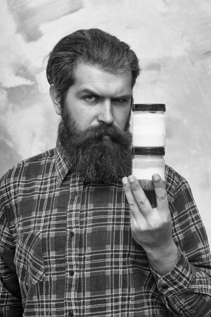 Serious bearded man, caucasian hipster, with long beard and moustache in red plaid shirt holding two cosmetic jars with colorful salt and cream on abstract yellow and pink wall background
