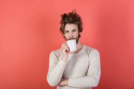 Cold and flu, single. Man with disheveled hair drink mulled wine. Morning with coffee or milk. Sleepy guy with tea cup on red background. Insomnia, refreshment and energy, copy space