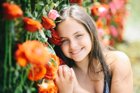 Floristic, floral decor, design, flower shop. Girl smile with red roses, beauty. Beauty, spring, summer season. Little child with flowers, spring. Valentines day, holiday celebration concept.