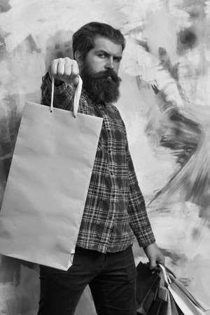 Serious bearded man, caucasian hipster, with long beard and moustache in red plaid shirt holding colorful paper shopping bags on abstract yellow and pink wall background
