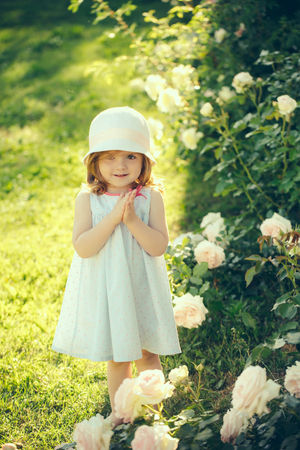 Girl in hat with praying hands in summer garden. Future and flourishing. Innocence, purity and youth concept. Germination and growth. Child standing at blossoming rose flowers on green grass.