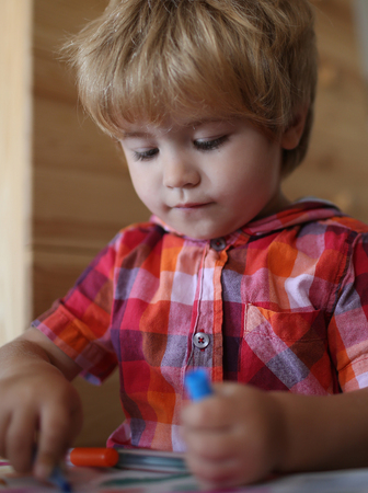 Small boy child drawing with colorful marker pen. Education and hobby. Childhood and happiness, learning. Painter child play with coloring book. Kid or blonde happy boy paint with felt pen.