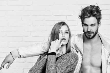 Young couple of handsome man or muscular macho in unzipped jacket with pretty cute girl or beautiful woman in knitted coat on white brick background