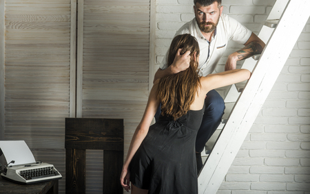 Bearded man hipster hug sexy woman with long hair. Sensual couple in love on ladder. Love, relations, relationship. Boyfriend, girlfriend, lovers, couple, family