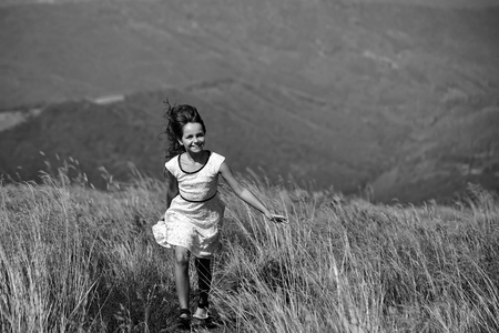 Small cute smiling brunette girl in white lace summer dress running in mountain valley with deep dry spikelet grass in spring sunny day outdoor on natural blue background, horizontal picture