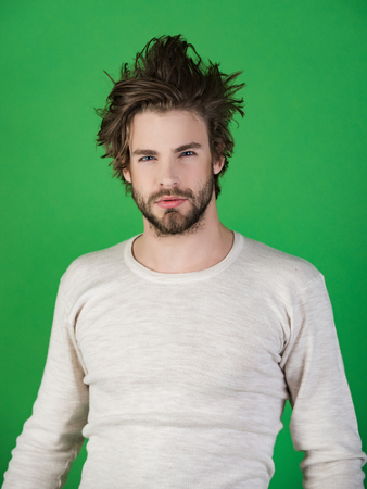 Morning wake up, everyday life. Man with disheveled hair in underwear. Insomnia, energy, single with uncombed hair. Sleepy man with beard on green background. Barber and hairdresser, male fashion.