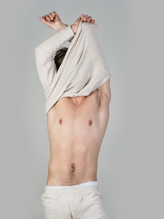 Sleepy man undress on grey background. Morning wake up, everyday life. Man with disheveled hair in underwear. Barber and hairdresser, male fashion. Insomnia, energy, single with uncombed hair.
