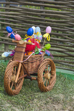 Easter decoration concept. Small bicycle with easter eggs. Wicker tricycle with basket on grass. Happy easter celebration. Spring, season, festival.