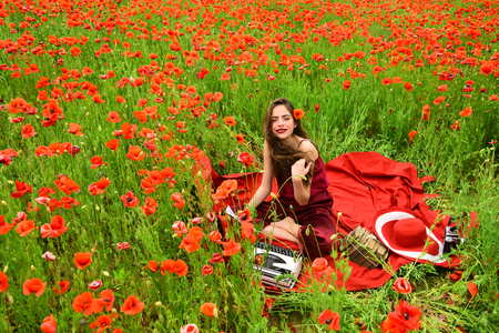 Woman writer in poppy flower field. Journalism and writing, summer. Opium poppy, agile business, ecology. Drug, narcotics, opium, woman with typewriter, camera, book. Poppy, Remembrance or Anzac Day.