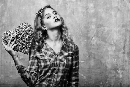 Pretty girl or beautiful woman with blond curly hair in stylish headband and violet plaid shirt with wicker heart for valentines day on beige wall background