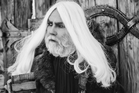 Druid old man with long grey hair and beard on serious face with wooden mug in hands outdoor on wood background with iron decoration 写真素材