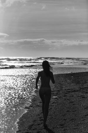 美しい女の子や美しい女性、セクシーなスリムなブルネット、海や海の海岸に沿って砂浜を走る黄色の水着で、太陽の輝きに輝く水面、牧歌的なバ