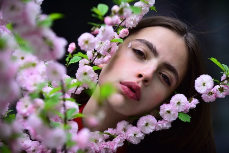 Girl with blossoming sakura on spring day. Young woman at cherry tree with pink flowers, beauty. Easter holiday celebration concept. Spring nature, beauty, new life, environment.