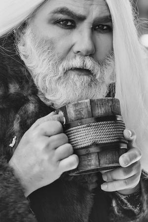 ぼやけた背景に手に木製のマグカップを持つしわの長い銀のひげと髪を持つドルイド老人
