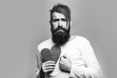 young bearded man with sad face holding red paper heart in studio on grey background, copy space Stok Fotoğraf