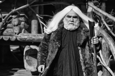 Brutal druid old man with long silver hair and beard in fur coat with axe in hand on log house background 版權商用圖片