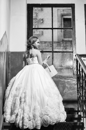 small girl kid with long blonde hair and pretty happy smiling face in prom princess white dress with basket standing near building glass big window on stairs