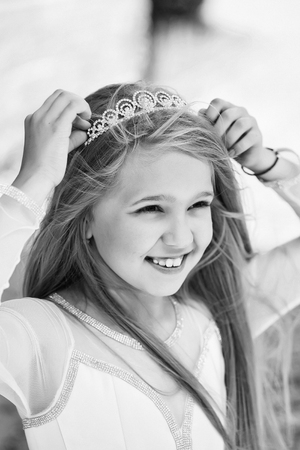 small girl kid with long blonde hair and pretty smiling happy face in dress and prom princess crown standing on white background, closeup