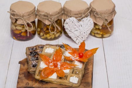 Wafers with tasty mixed nuts, cream topping garnished with flowers and heart symbol.