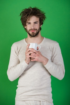 Man with disheveled hair drink mulled wine. Morning with coffee or milk. Cold and flu, single. Happy guy with tea cup on green background. Insomnia, refreshment and energy.