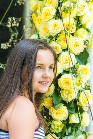 Cheerful charming young girl florist stand at bunches of yellow roses in flower shop.