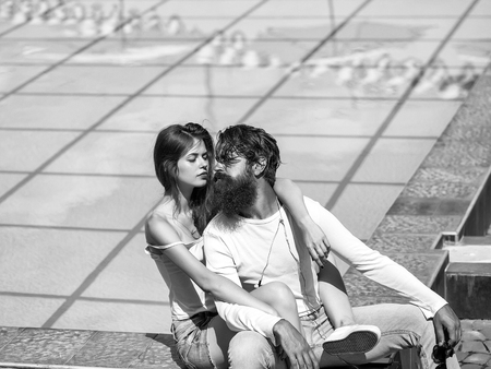 Young couple of pretty woman and bearded man enjoy sunny summer vacation near swimming pool