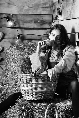 Pretty girl teenager young woman cookee helper in apron eats bun bread on straw bales with wicker basket on rustic background