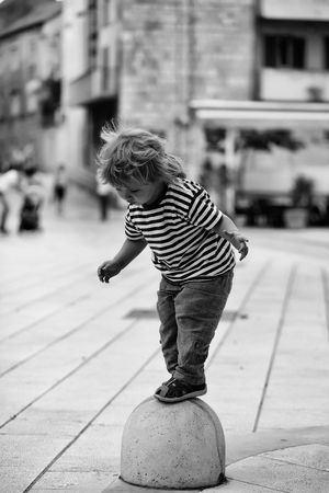 Cute baby boy child with curly blond hair in striped shirt stands on concrete semisphere bollard on street pavement Stockfoto