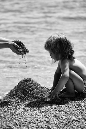 Mignon bébé enfant avec les cheveux blonds bouclés assis sur la plage et joue avec galets sur fond bleu mer sur l & # 39 ; été journée ensoleillée Banque d'images - 96076731