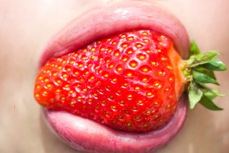 Summer, fruit, berry, harvest season. Strawberry in mouth with rosy lips, makeup. Beauty, lipstick, lip gloss, make up. Food, healthy diet, dieting. Nutrition, health, vitamin. 版權商用圖片