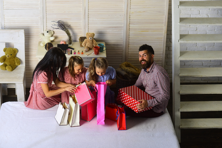 Celebration and shopping concept. Mother, father and daughters with shopping bags and packs. Man, woman and adorable children with gifts at home. Family with cheerful faces open presents at home.