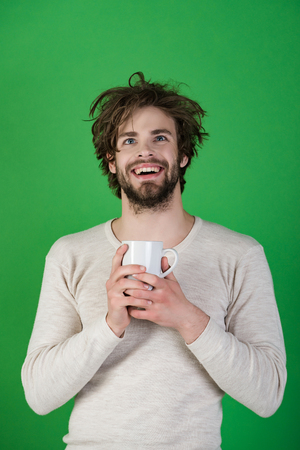 Morning with coffee or milk. Cold and flu, single. Happy with a teacup on a green background. A man with disheveled hair drink mulled wine. Stock Photo