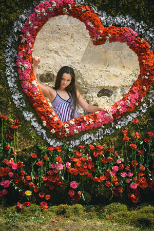 Love heart floral frame with litte girl. Love symbol of rose flowers arrangement and young woman. 스톡 콘텐츠