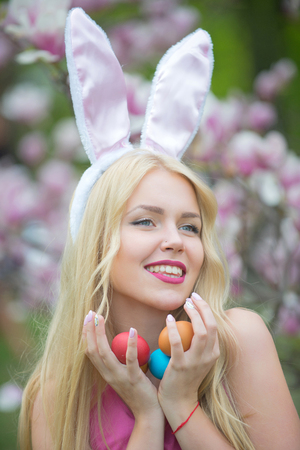 Happy easter concept, woman in blossoming magnolia flower, spring. Spring, nature, season. spring holiday celebration. Sensual woman at magnolia with colorful eggs. Easter eggs at woman in bunny ears.