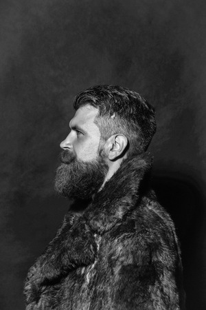 Bearded handsome young man hipster with beard and moustache in brown fur coat on black background in profile Stok Fotoğraf