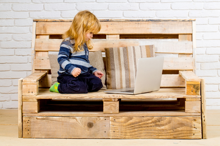 Small boy blogging on bench, online buy. child with laptop and mobile phone, education. Social network and new technology. School and communication. Kid at computer with cell phone, sms and 4G. Stock Photo