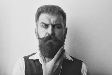 Bearded man, long beard, brutal caucasian hipster with mustache with serious face in shirt and brown waistcoat on white background, unshaven with stylish hair getting haircut, copy space