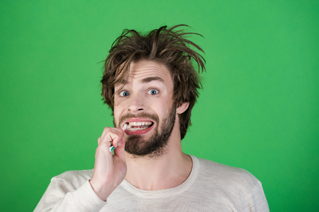 Happy man with beard grooming on green background. Morning washing, wake up, everyday life. Hygiene, teeth whitening. Stomatology and dental care. Man with disheveled hair in underwear brush teeth.