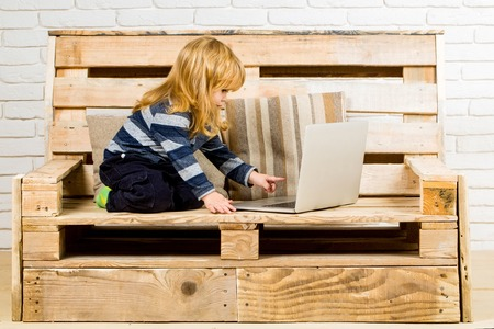 Kid at computer with cell phone, sms and 4G. School and communication. child with laptop and mobile phone, education. Social network and new technology. Small boy blogging on bench, online buy. Stock Photo