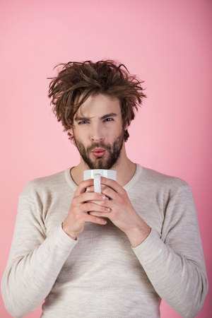Morning with coffee or milk. Sleepy guy with tea cup on pink background. Stock fotó