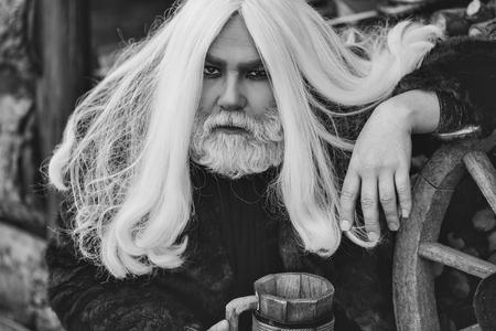 長い灰色の髪と毛皮のコートに長い灰色の髪とひげを持つドルイドの古いひげの男は、屋外の車輪の近くに手で木製のマグカップと毛皮のマグカッ