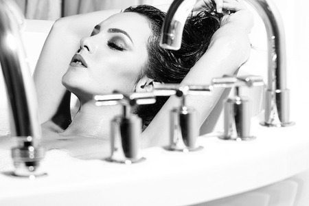 白い背景にクロムコックの水と泡でバスタブに横たわっている濡れた長い巻き毛を持つ1つの魅力的な情熱的な若いブルネットのセクシーな裸の女性