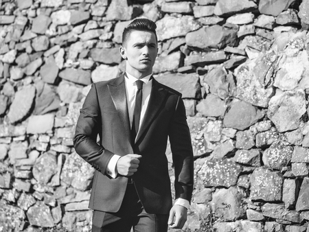 Man young handsome elegant model wears suit white shirt with black skinny necktie looks into distance poses outdoor on masonry background