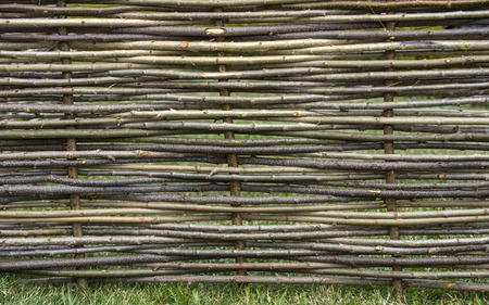 Garden decor, barrier, border, boundary. Fence of wooden twigs. Natural tree trunk texture. Spring, summer season
