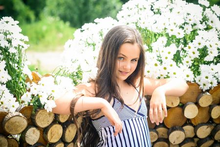 Beauty, look, hair. Girl pose with daisy flowers on sunny day, spring. Little child at wooden fence with camomile flowers, beauty. Spring, summer, romance. Stok Fotoğraf