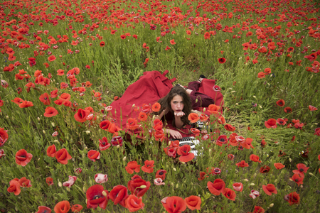 Woman writer in poppy flower field. Drug, narcotics, opium, woman with typewriter, camera, book. Poppy, Remembrance or Anzac Day. Opium poppy, agile business, ecology. Journalism and writing, summer. Reklamní fotografie