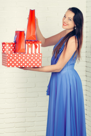 christmas, boxing day, happy woman with red present box in blue dress on white brick wall background, holiday and celebration, new year and birthday party