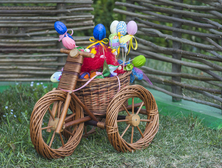 Happy easter celebration. Wicker tricycle with basket on grass. Small bicycle with easter eggs. Spring, easter season, festival.