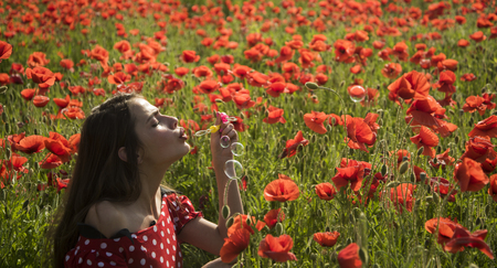 Drug, opium, narcotics, carelessness. Summer, spring, poppy flower. Opium poppy, youth, freshness, ecology, woman. Poppy, Remembrance day, Anzac Day. Woman blow bubble in poppy field, dreams, wishes.